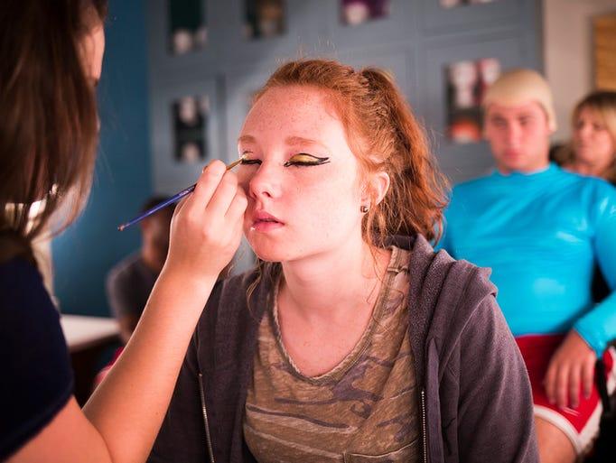 Assistant makeup artist Cara Druck, left, works on