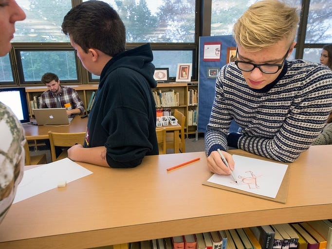 Gabe Fryar, right, age 17 works on a drawing while