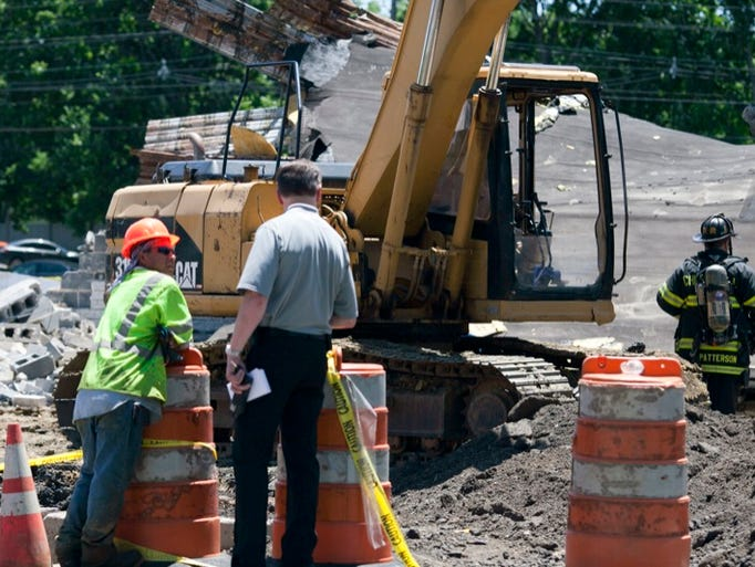 Emergency personnel on the scene of a building collapse that left one dead, Friday, June 20, 2014 in Cherry Hill. The old Blockbuster Movies store was in the last stages of demolition when the accident occurred.