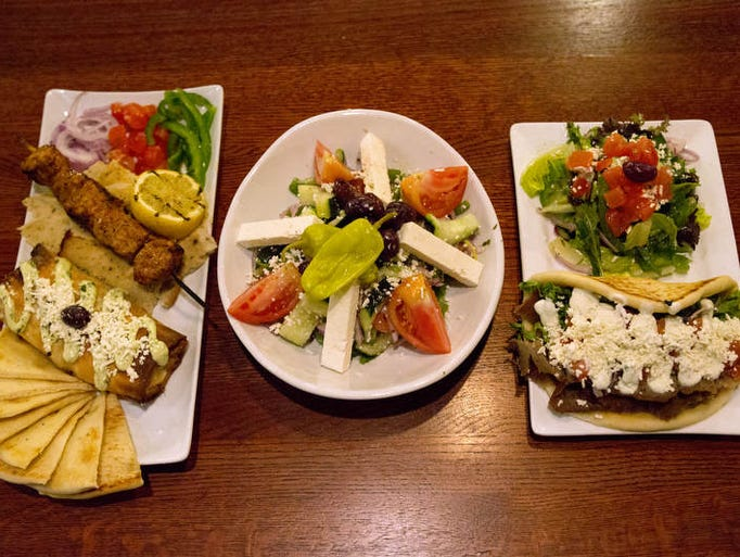 From left, the Greek Peak combo of spanakopita, pork souvlaki and chicken gyro meat, Horiatiki salad with feta and the traditional gyro pita at Akropolis in Fort Collins Monday, March 3, 2014. The Greek restaurant is now open on 4235 S. College Avenue.