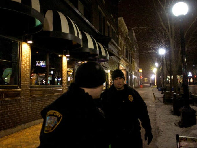 Iowa City Police officers Alex Stricker, left, and Rob Cash patrol the Pedestrian Mall late Saturday night, March 23, 2013.