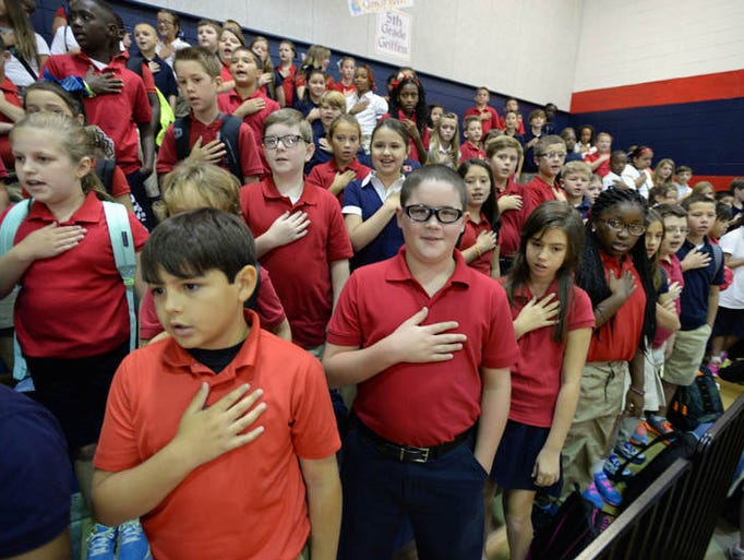 Students recite the Pledge of Allegiance in the gym at North DeSoto upper elementary in Stonewall, La during the first day of school Tuesday August, 5, 2014.