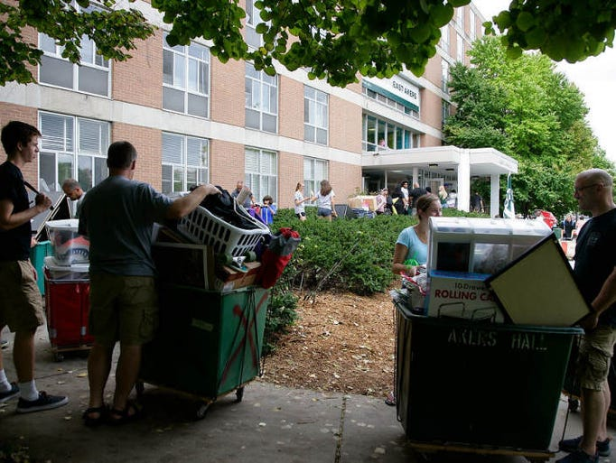 New MSU dorm residents and their helpers wait as they line up to move into Akers Hall Sunday, Aug. 24, 2014, in East Lansing, Mich. Thousands of freshmen moved in Sunday.