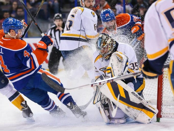 Mar 18, 2014; Edmonton, Alberta, CAN; Nashville Predators goalie Pekka Rinne (35) makes a save as Edmonton Oilers left wing Taylor Hall (4) tries to score during the first period at Rexall Place.