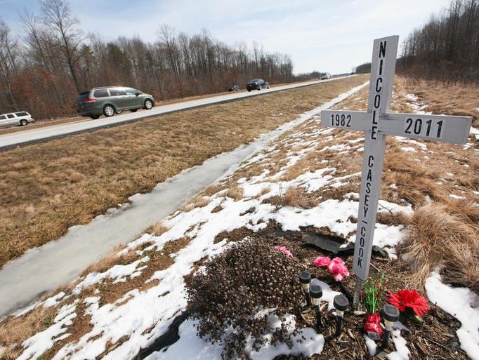 A cross sits off the southbound lanes of Del. 1 where a woman was killed in 2011.
