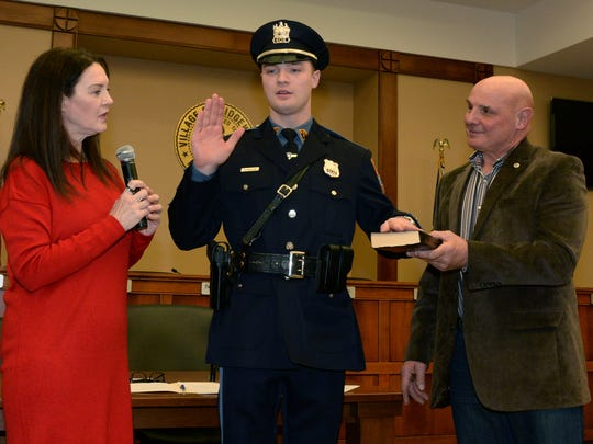 Ridgewood Mayor Susan Knudsen swearing in her son Police Officer Zachary Knudsen in 2017. His father John Knudsen holds the bible.