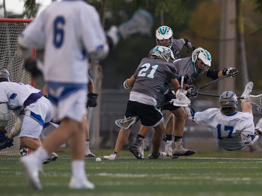 Barron Collier's Connor McGraw (17) gets checked by