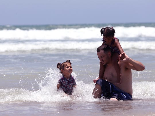 Higher-than-normal tides didn't deter beach-goers at Bob Hall Pier on Thursday, June 22, 2017. Travis Arnaud, of Dallas, plays with his daughters Julia Arnaud (left), 3, and Jolie Arnaud, 2, in the surf, which was also stronger than usual.