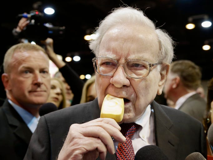 Berkshire Hathaway Chairman and CEO Warren Buffett eats an ice cream bar while touring the exhibition floor prior to the annual shareholders meeting on in Omaha, Neb.