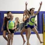 Elmira Gymnastics Club members Grace Freeman, front, and her Level 4-8 teammates do carthweels during a recent practice.