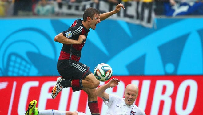 Michael Bradley of the United States challenges Thomas Mueller of Germany during the 2014 FIFA World Cup Brazil group G match between the United States and Germany at Arena Pernambuco June 26.
