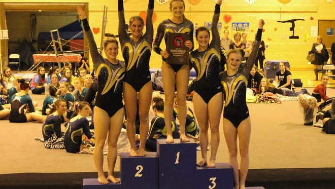The Waupun gymnastics team poses on the podium after qualifying for state on Friday at Whitefish Bay.