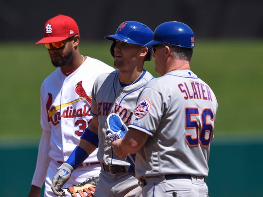 New York Mets center fielder Brandon Nimmo (9) speaks with assistant hitting coach Tom Slater (56) after being hit by a pitch from St. Louis Cardinals starting pitcher Carlos Martinez (18) (not pictured) during the fifth inning at Busch Stadium.