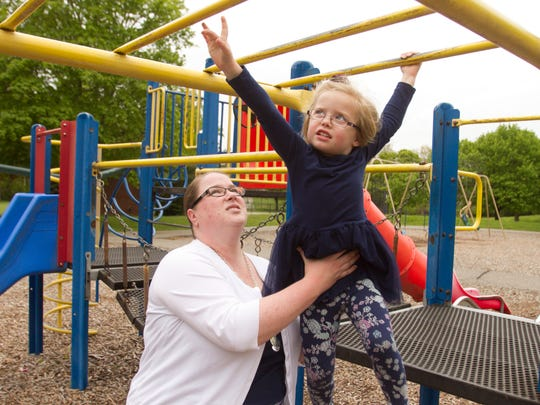 Nanny Candace Streng lends support to 4-year-old Emily Kovalik on playground equipment at McHattie Park in South Lyon Thursday, May 11, 2017. Streng nannies twins, Emily and her sister Sarah, meeting regularly with a moms group who've banded together to support Streng with a GoFundMe page and June 17 fundraiser to help with expensive cancer treatments.