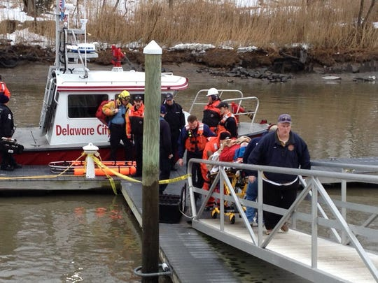 Injured person from dredge in Delaware River is taken from boat to ambulance in Delaware City.