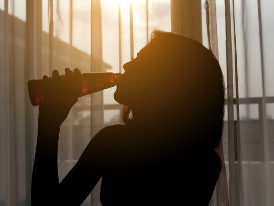 Silhouette shot of a female drinking red wine in a  room
