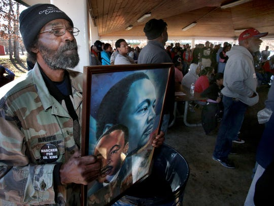Johnny Reed holds up images of Dr. Martin Luther King