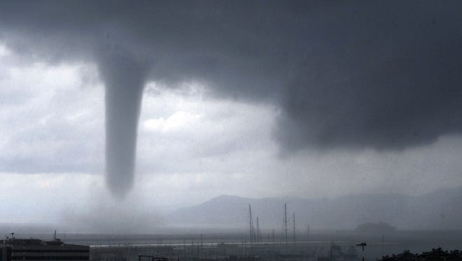 Tano Pecoraro, AP A tornado approaches Genoa, Italy, on Tuesday. Tornadoes and thunderstorms hit the city and the Liguria region coast. A tornado is seen approaching the costal city of Genoa, in Northern Italy, Tuesday, Aug 19, 2014. At right, in background, the profile of the Costa Concordia cruise liner wreck which was towed to Genoa for scrapping. Tornadoes and thunderstorms hit Genoa and the Liguria region coast Tuesday, causing damages to seaside cabins and floods but no victims. (AP Photo/Tano Pecoraro)