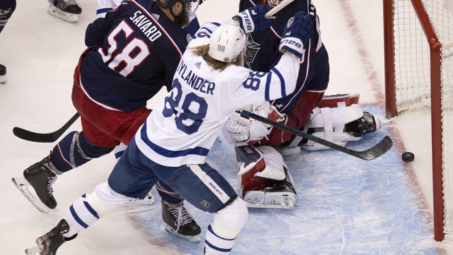 William Nylander (88) celebrates teammate Zach Hyman, not pictured, beating Blue Jackets goaltender Elvis Merzlikins for the tying goal with 23 seconds left in regulation Friday night, as the Maple Leafs erased a three-goal deficit in about 3½ minutes.