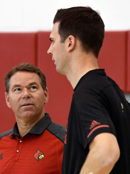 Louisville's acting athletic director Vince Tyra, left, speaks to interim men's basketball head coach David Padgett before the start of NCAA college basketball practice, Wednesday, Oct. 4, 2017, in Louisville, Ky. (AP Photo/Timothy D. Easley)