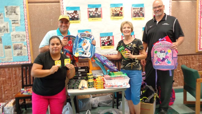 Rotary president Keith Buchhalter, back left, Edwina Jauregui,front left, and Rotarians Linda Gault, middle, and Kevin Boyer survey the pile of supplies and backpacks.