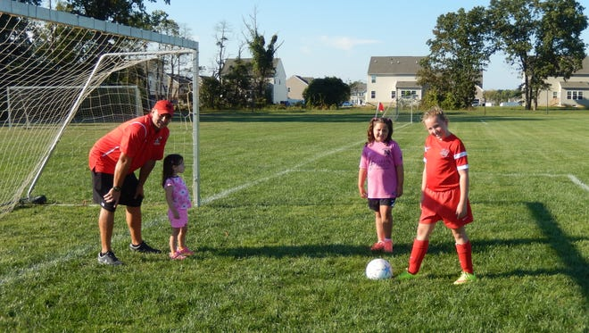 A.J. Ciabattoni and his daughters Brooke 10, Emma, 7, and Ava, 3, play on a soccer field. He is a coach for his daughters' sports, including soccer.