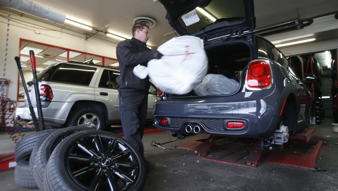 FILE - In this Nov. 10, 2014 file photo, tire installer Shawn Dutton places summer tires back in customer's car at a tire shop in southeast Denver.