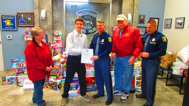 First Lt. Joel Allen, middle, presents Hartland Township's Doulgas Adams, second from left, a certificate of appreciation for his 11-years of dedication to the Toys for Tots program. Also pictured are Alice Adams, left, Toys for Tots representative Mike Lenahan and Lt. Kevin Caldwell.