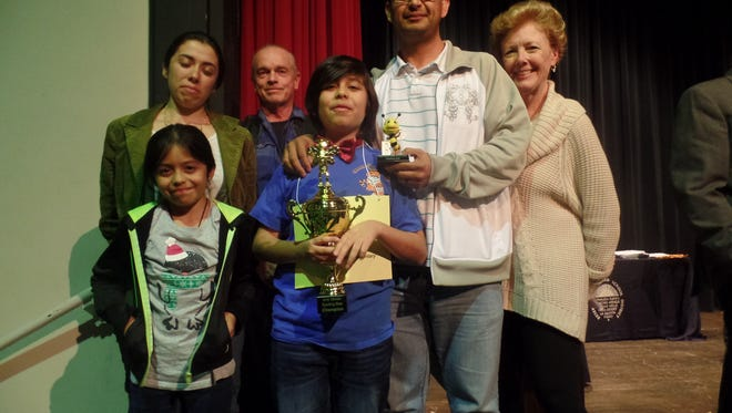 Aiden De La Cruz (center), a fifth grader at Harry S. Truman Elementary School, won this year's spelling bee. He poses with his trophy, parents, sister, teacher David Lawson (second from right) and principal Carol Bishop (far right).