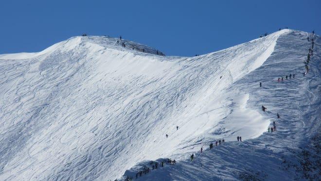 A line of skiers and snowboarders ascends Highlands Bowl at Aspen Highlands Ski Resort.