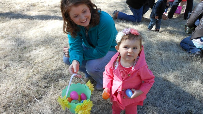 Lila Miles and her mom Aleah Miles of Ruidoso show off their take from the Cedar Creek Easter egg hunt.