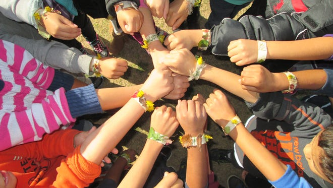 Members of a La Semilla Food Center youth group show off bracelets made from organic materials.