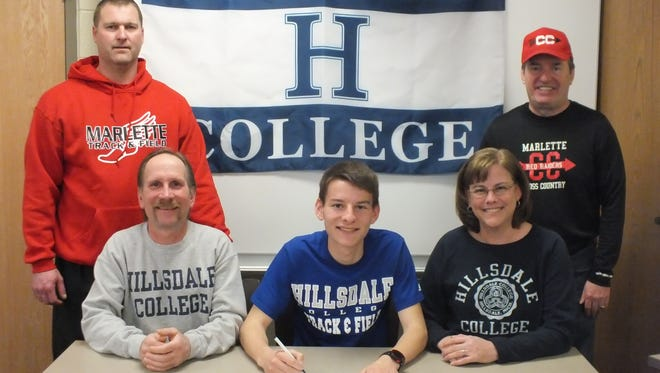 Eric Poth (middle) signs his Letter of Intent to Hillsdale College alongside his father, Ron (front left), mom, Wendy (front right) and track coach Chris Storm (back left) and cross country coach Chris Titus (back right).
