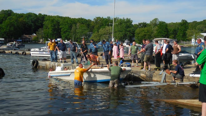 Emergency personnel load a capsized boat onto a trailer.