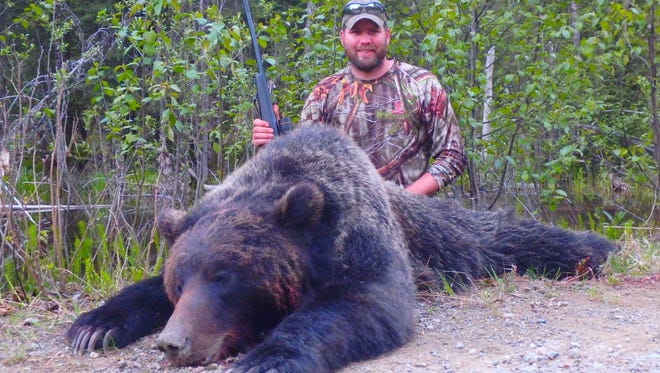 Ken Olson of Manitowoc shows the grizzly bear he shot this spring with the help of Eric Hanson of McGregor River Outfitters in British Columbia, Canada. There were some tense moments when the grizzly charged, but Olson dropped him with his last shot. The grizzly measured 7 feet tall.