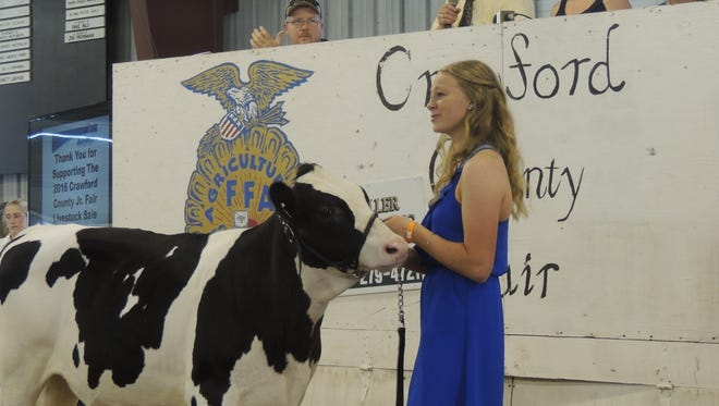 Fair Queen Taylor Lutz sells her reserve champion dairy feeder for a record $1,900 at the Junior Fair Livestock Sale on Saturday morning.