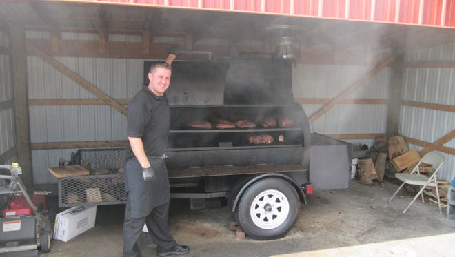 "Kyle ""Tex"" Mayo, co-owner of CJ's BBQ Smokehouse, is pictured while he checks meat on the smoker."