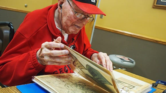 Francis Graf, who turns 100 on Sept. 26, pages through a scrapbook of his time in the military.