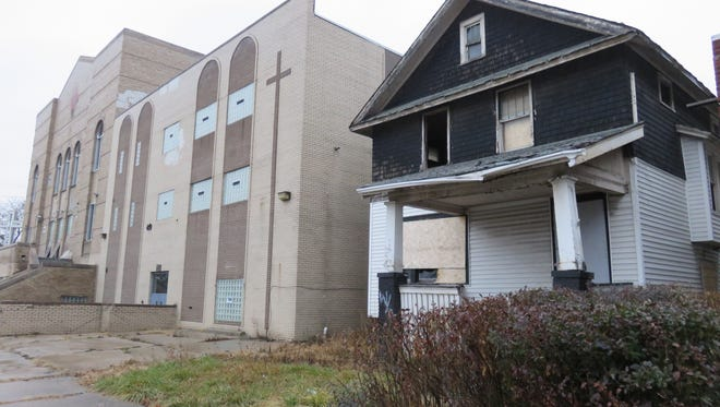A dilapidated house sits next to the former Tried Stone Baptist Church, which Boy Scout Nick Stanley is helping a Detroit nonprofit to renovate. Nick plans to build a playground there with community support.