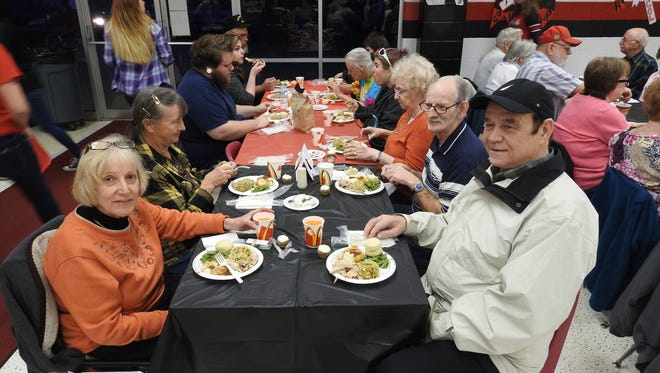 Gail and John Jackson, left and right, of West Lafayette, enjoyed an early holiday dinner Thursday night during the 13th Annual CommunityThanksgiving Dinner at Coshocton High School.