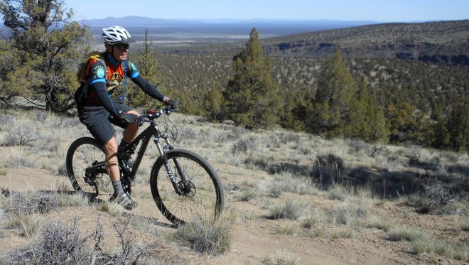 In this April 15, 2016 photo, Mark Johnson rides his mountain bike along Horse Ridge East, in Bend, Ore.