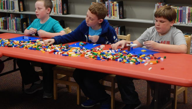 Mason Blake, Jonathan Hargrove, and James Garrett work to construct their dog traps at Friday's Lego Quest program.