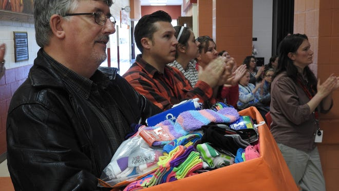 Pastor Starkey Lawrence, of Shepherd's Christian Assembly, holds socks donated to his church by Coshocton Elementary students, who collected them through their annual Socktober drive.