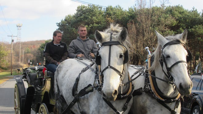 A horse-drawn carriage pulls up to Mr. Ed's with a special passenger Sunday.