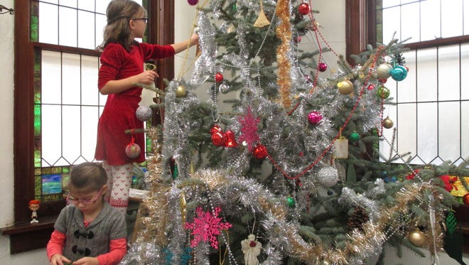 A favorite kids' tradition at Christ the King Fellowship (Presbyterian Church) in Spencer is decorating their freshly cut Christmas tree. The tree is hardly visible in places but they had a wonderful time decorating it.  Pictured here are Emma Drake and Ashlynn Bossard on the ladder.