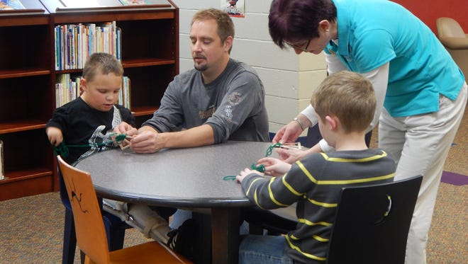 Library aide Debbie Long demonstrates to Drew Gatton and Levi Lamb how to weave their trees.