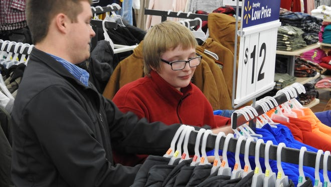 J.R. Corder, right, of Coshocton, picks out a new winter coat at Walmart Monday with help from volunteer Phil Goerig through the Salvation Army's annual Christmas Castle program.