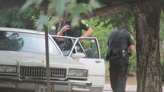 """Asheville police officers investigate the scene after Jai """"Jerry"""" Williams was shot by an officer July 2 at Deaverview Apartments."""
