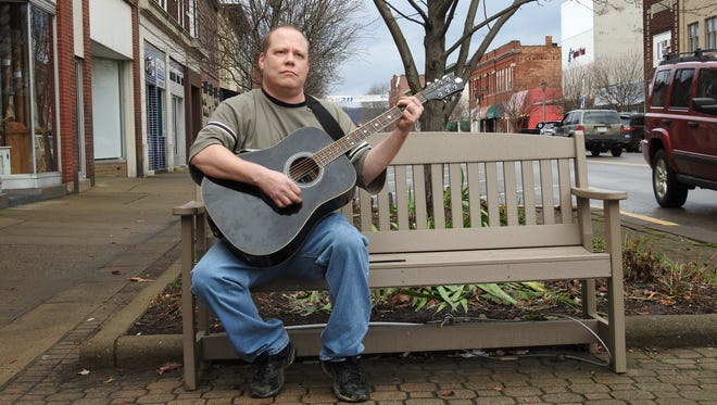 Jason Mathews of Coshocton took advantage of spring-like weather and a break between rainstorms to play guitar outside his downtown apartment Thursday. Temperatures hit the low 60s locally.