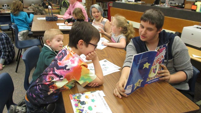 Cameron Greeson, a senior at Spencer-Van Etten High School, reads a Dr. Seuss book to children in a kindergarten class. Other seniors in the background are Amanda Siegard and Daniel Deppe.